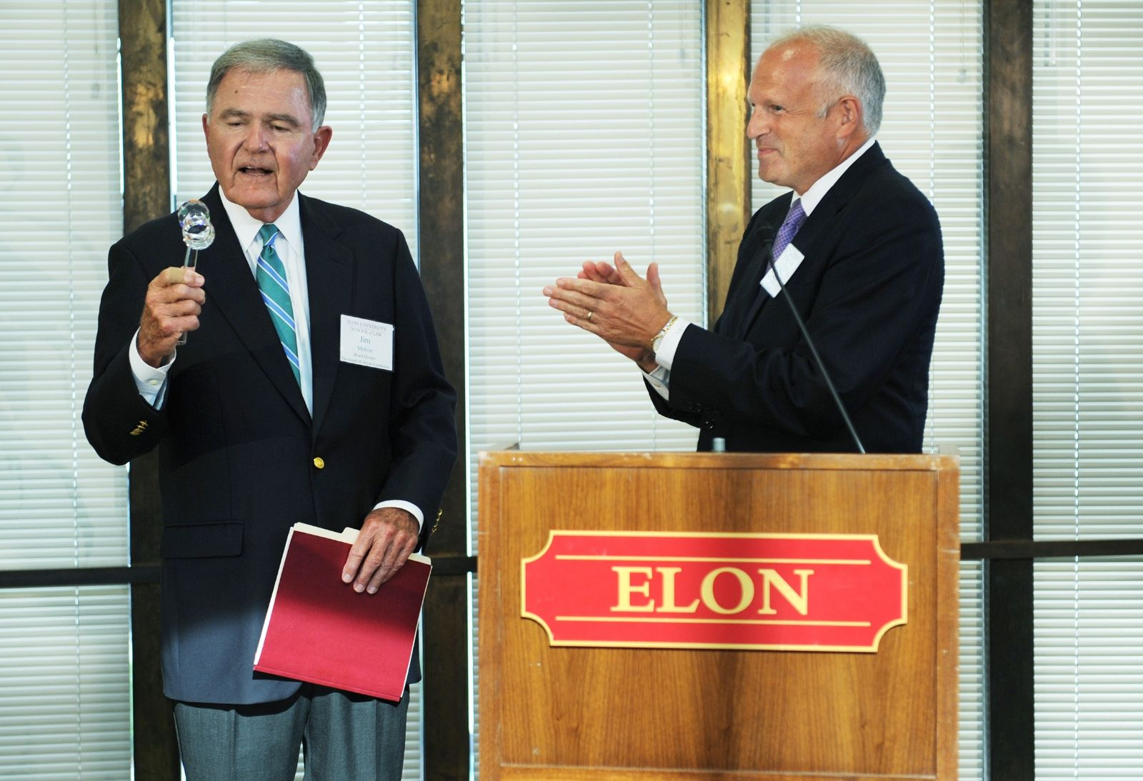 Jim Melvin, left, receives a crystal gavel from Elon president Leo M. Lambert