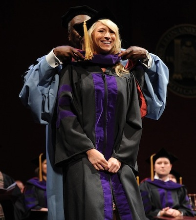 Ivy Oakley of the Class of 2011 is hooded by Dean George Johnson